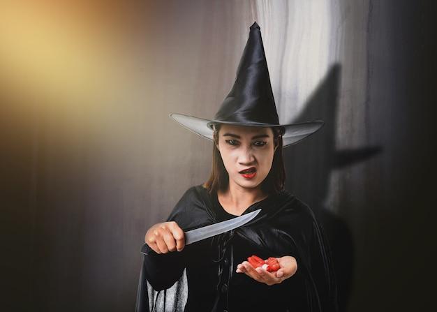 Frau im schwarzen furchtsamen hexenhalloween-kostüm, ein messer mit alter zementwand halten