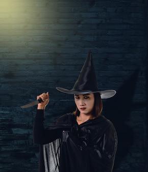 Frau im schwarzen furchtsamen hexenhalloween-kostüm, ein messer mit backsteinmauer des ancie halten
