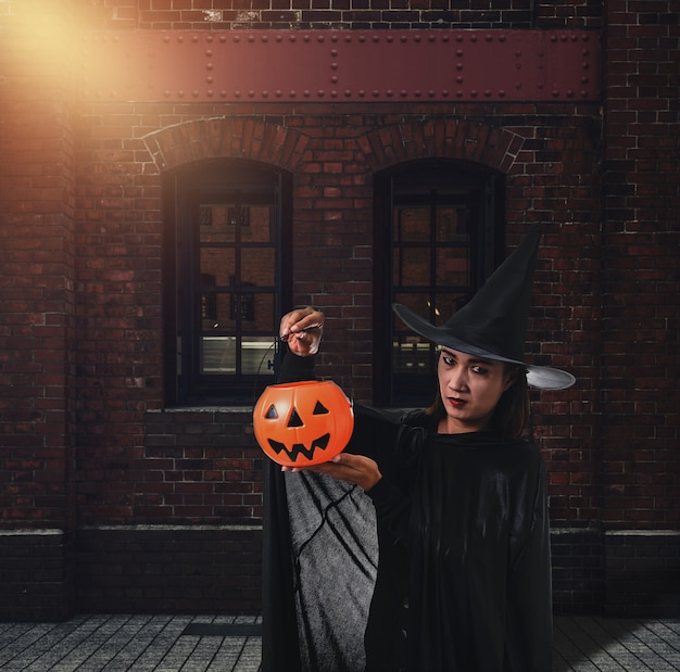 Frau im schwarzen furchtsamen hexenhalloween-kostüm mit alter backsteinmauer des alten schlosses der hexe