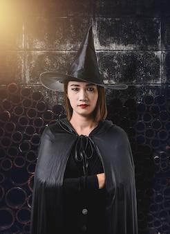 Frau im schwarzen furchtsamen hexenhalloween-kostüm mit alter zementwand