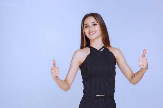 Frau im schwarzen hemd, das daumen hoch zeichen tut.