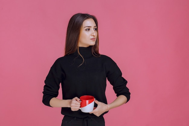 Frau im schwarzen hemd, das eine kaffeetasse hält und lächelt.