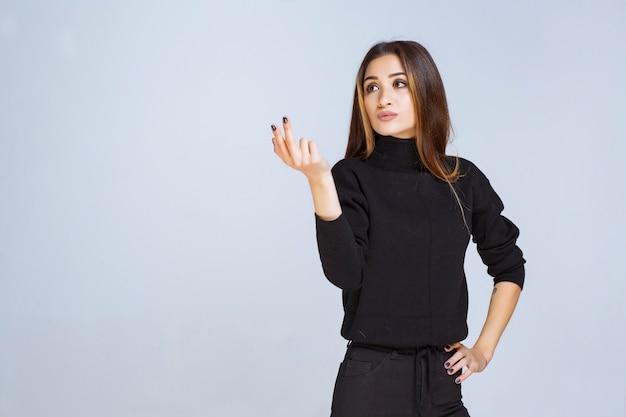 Frau im schwarzen hemd, das friedens- und freundschaftsbotschaft sendet.