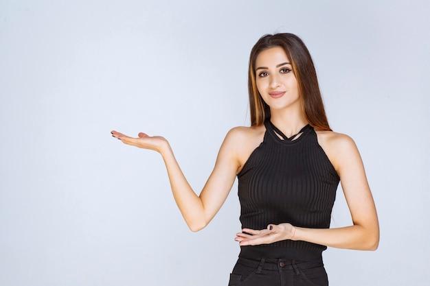 Frau im schwarzen hemd, das hand öffnet und etwas hält oder präsentiert.