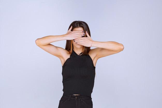 Frau im schwarzen hemd, das ihr gesicht bedeckt und versteckt.