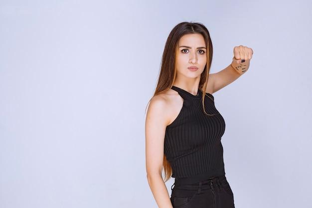 Frau im schwarzen hemd, das ihre fäuste demonstriert.