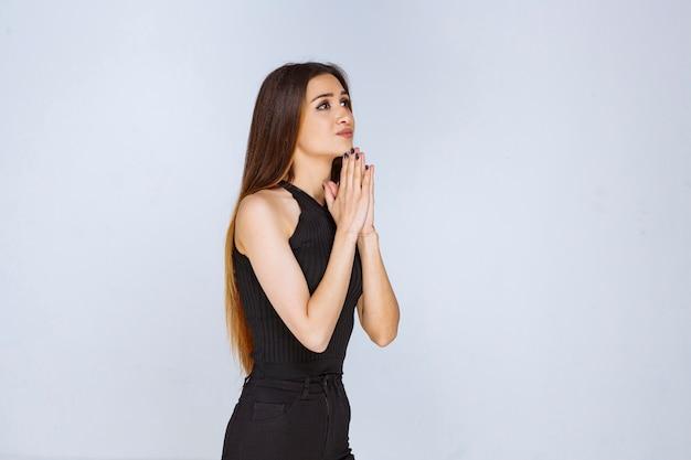 Frau im schwarzen hemd, das ihre hände vereinigt und betet.