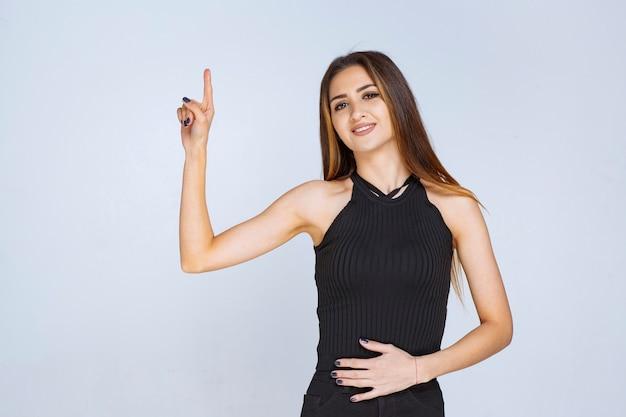 Frau im schwarzen hemd, das irgendwo mit finger zeigt.