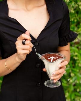 Frau im schwarzen hemd, das milchigen sahnetiramisu mit kakaopulver innerhalb des glases isst.