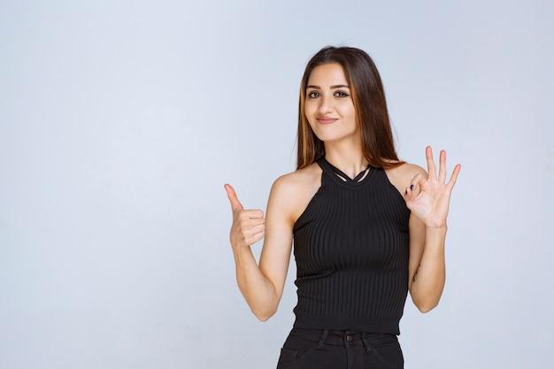Frau im schwarzen hemd, das positives handzeichen macht.