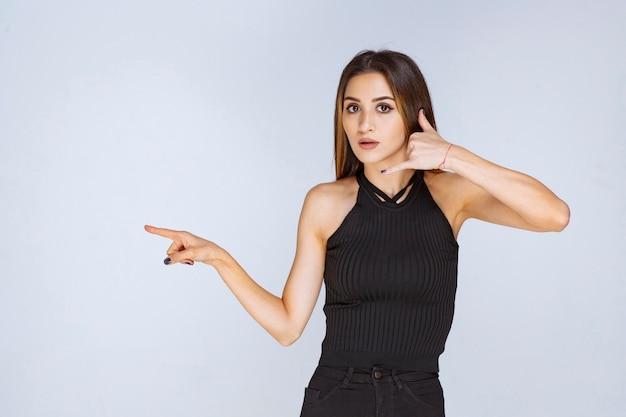 Frau im schwarzen hemd, das rufzeichen macht.