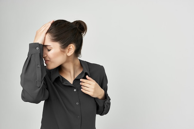Frau im schwarzen hemd, das seinen kopf deprimiert hellem hintergrund hält. foto in hoher qualität