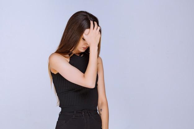 Frau im schwarzen hemd, das traurig fühlt oder kopfschmerzen hat.