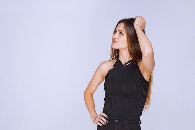 Frau im schwarzen hemd, das verführerische und ansprechende posen gibt.