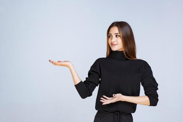 Frau im schwarzen hemd, die auf etwas links zeigt.