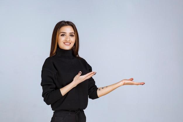Frau im schwarzen hemd, die auf etwas rechts zeigt.