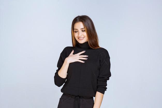 Frau im schwarzen hemd, die auf sich selbst zeigt.