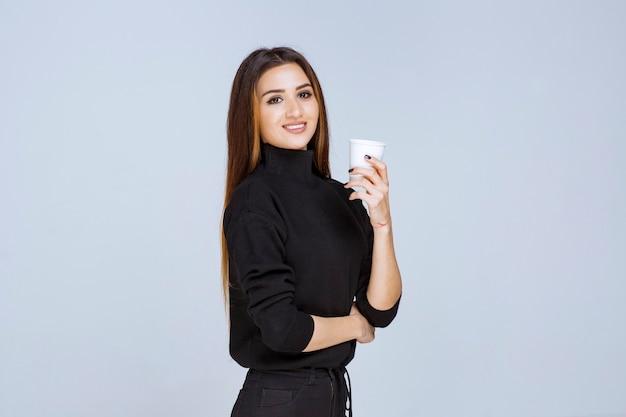 Frau im schwarzen hemd, die eine wegwerfkaffeetasse hält und sie fördert.