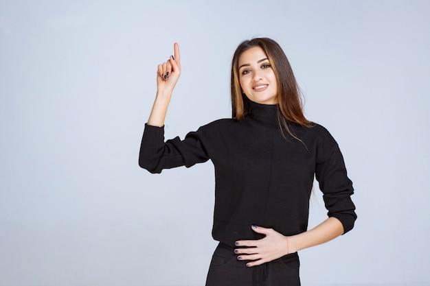 Frau im schwarzen hemd, die etwas oben zeigt.
