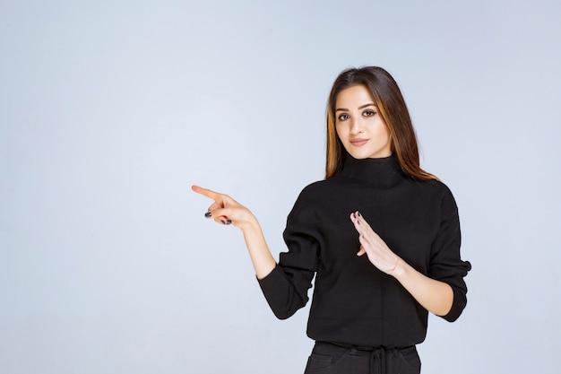 Frau im schwarzen hemd, die nach links zeigt und ihre gefühle zeigt.