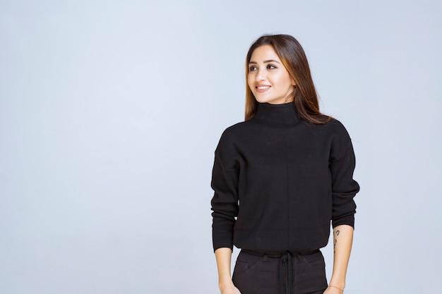 Frau im schwarzen hemd, die neutrale und kokette posen gibt.