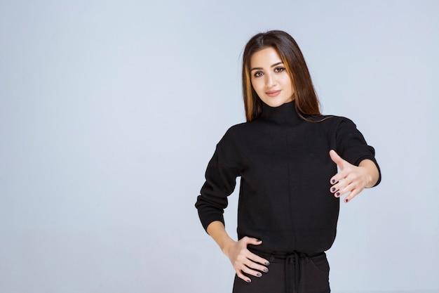 Frau im schwarzen hemd mit positivem handzeichen.