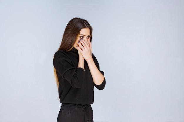Frau im schwarzen hemd sieht begeistert und verängstigt aus.