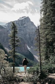 Frau im schwarzen hemd und in der weißen hose, die auf grünem grasfeld nahe grünen bäumen stehen