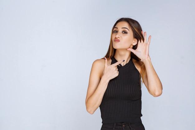 Frau im schwarzen hemd zeigt ihr ohr, als sie probleme mit dem hören hat.