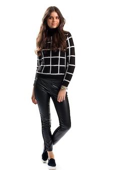 Frau im schwarzen karierten sweatshirt. slip-ons und hosen. freizeitkleidung für den herbst. nagelneue lederhose.