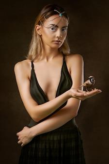Frau im schwarzen kleid, das braunen vogel hält