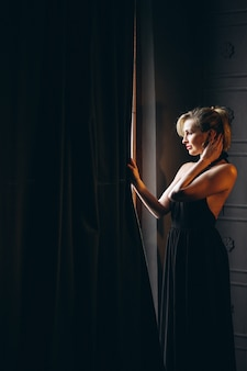 Frau im schwarzen kleid, das das fenster bereitsteht
