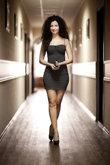Frau im schwarzen kleid, das entlang korridor geht