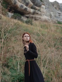 Frau im schwarzen kleid in der gebirgsreiseweglandschaft