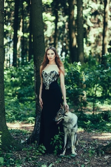 Frau im schwarzen kleid mit hund