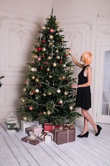 Frau im schwarzen kleid nahe geschmücktem weihnachtsbaum