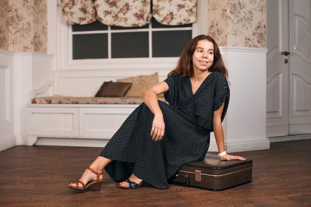 Frau im schwarzen kleid sitzt auf ihrem koffer.