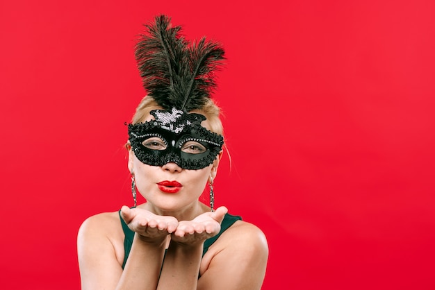 Frau im schwarzen kuss der schwarzen karnevalsmaske