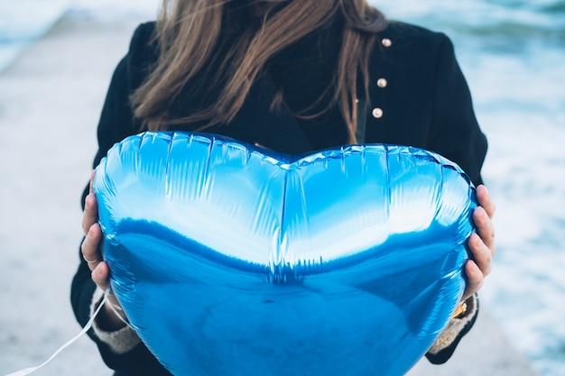 Frau im schwarzen mantel, der einen ballon in form des herzens hält