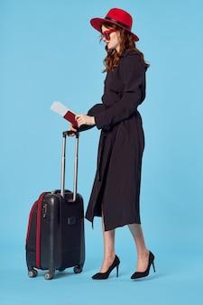 Frau im schwarzen mantel gepäck flughafen reise blauen hintergrund geschäftsreise