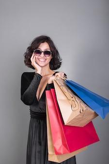 Frau im schwarzen mit bunten einkaufstaschen
