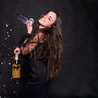 Frau im schwarzen mit champagnerflasche und -gläsern