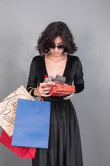 Frau im schwarzen mit geschenken und einkaufstaschen