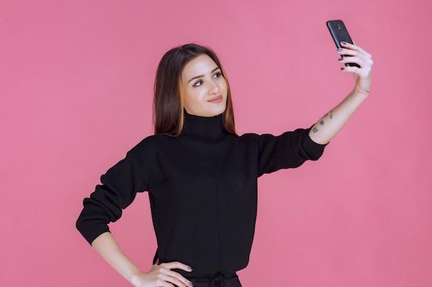 Frau im schwarzen pullover, der ein smartphone hält und ihr selfie nimmt.