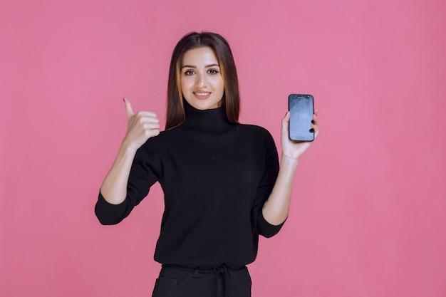 Frau im schwarzen pullover hält ein smartphone und macht daumen hoch.