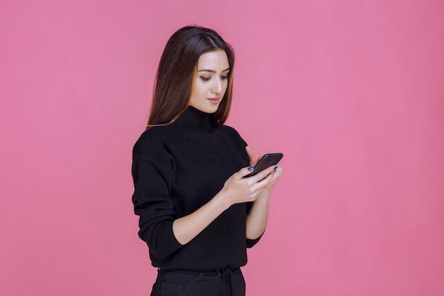 Frau im schwarzen pullover hält ein smartphone und sms oder überprüfung der sozialen medien.