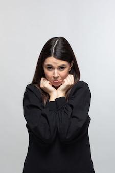 Frau im schwarzen pullover zeigt angst ressentiments