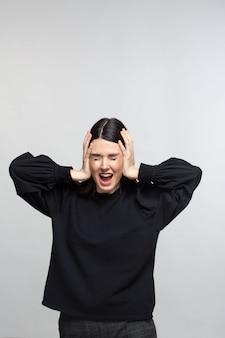 Frau im schwarzen pullover zeigt bedrängnis