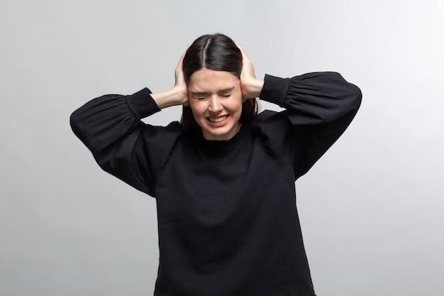 Frau im schwarzen pullover zeigt kopfschmerzen