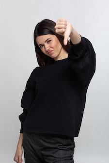 Frau im schwarzen pullover zeigt schläge nach unten